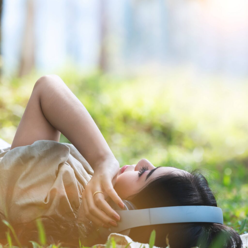young woman listening the music on the green grass at the garden in the spring season
